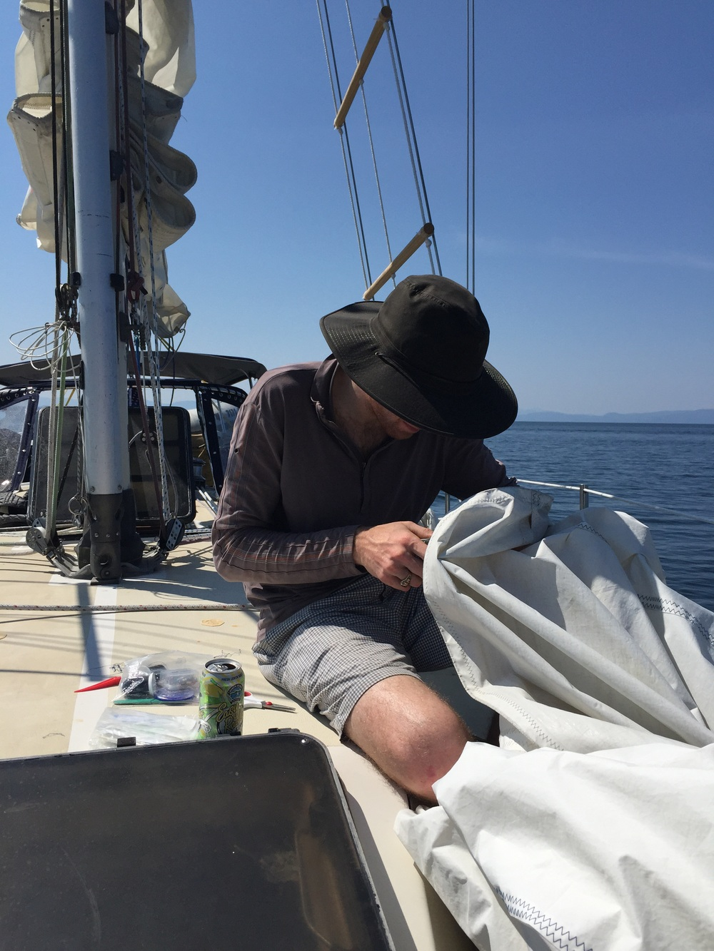 Kevin sews our ripped sail