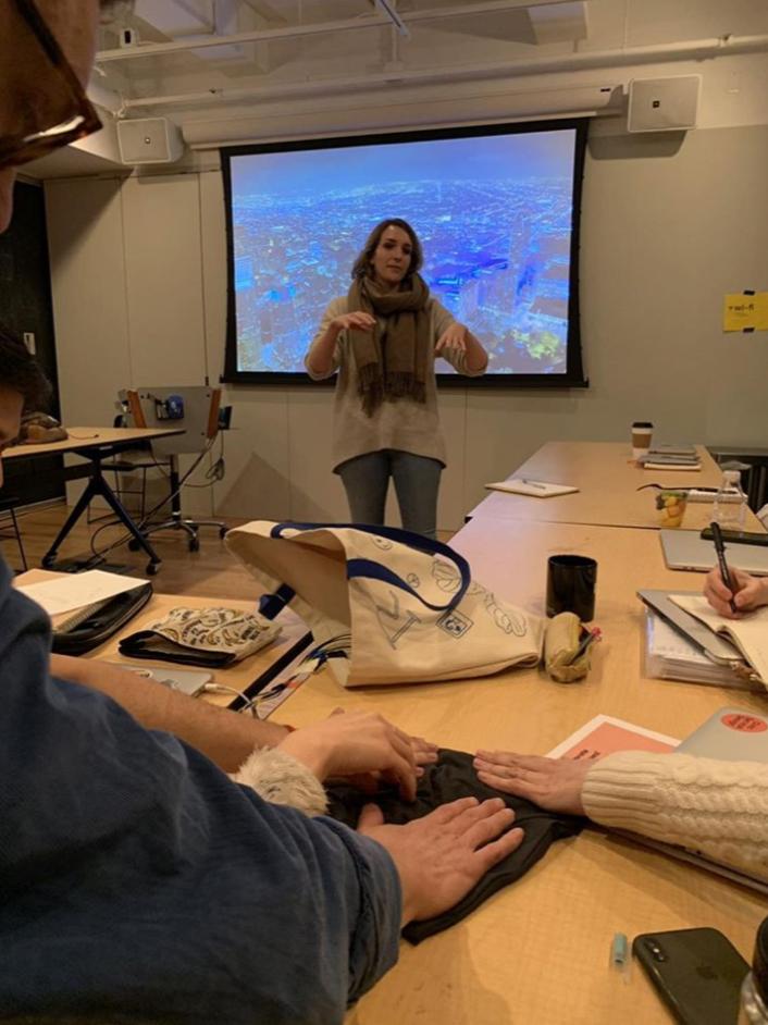 Colleagues feeling a small prototype using vibrating motors during a progress presentation.