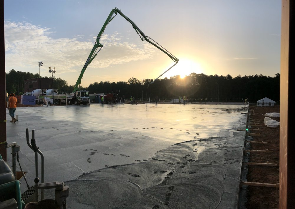 The sun rises over the freshly poured concrete slab for the mult-purpose room and gym. Photo credit: Brian Grady
