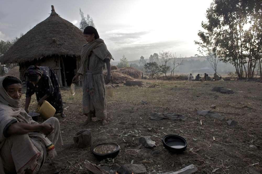 Relatives of Etinesh, 11 years old, and Torokan, 8 years old, who will be sold into marriage that day, prepare meals to be served during the marriage celebration at dawn in a village in the Northern Amhara region of Ethiopia.