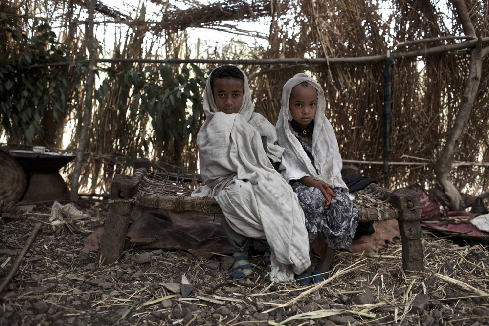 Ambaun, 9 years old, (left) and Deghe, 7 years old, (right) sit in their matrimonial tent before their wedding celebration commence in a village in the Northern Amhara region.