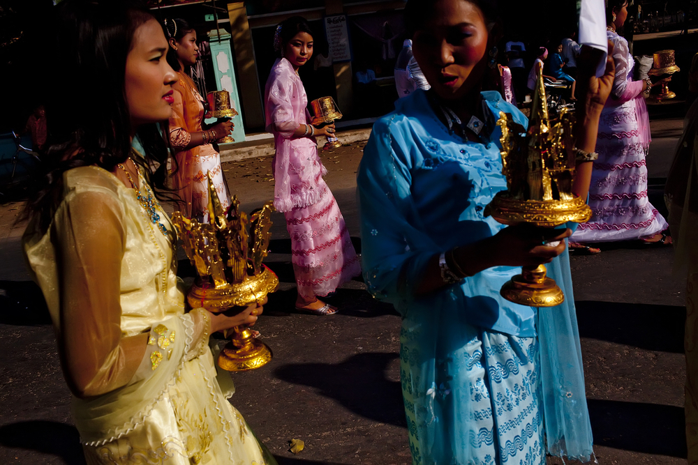 Burmese women pass dressed in traditional clothing pass through the streets of Bagan during a wedding.