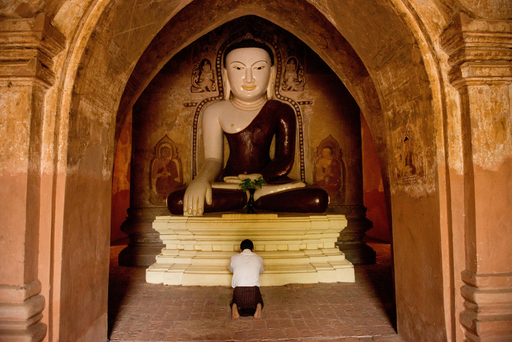 Gigantic buddhist statue dwarfs the visiting tourists at the Simyarshin stupa in Bagan.