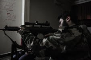 19 year-old Becker aims down a new rifle in an rebel held apartment in Aleppo.