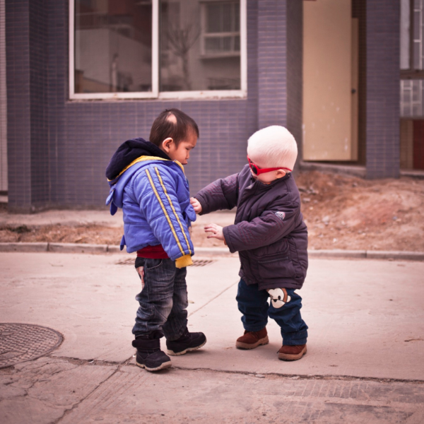 Above:  Jian Ang (left) helps Jianshan do up his jacket at the orphanage in Zhengzhou.