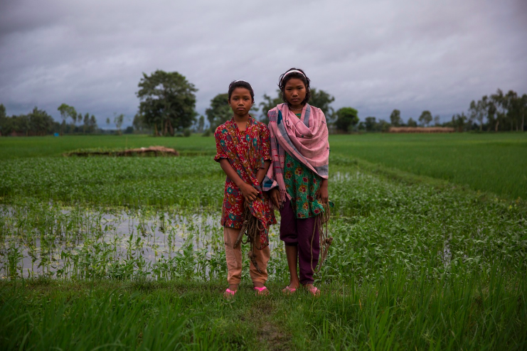 ABOVE: Sisters Lobar Rani Bormoni, 11, and Shapla Rani Bormoni, 12, stand in a paddy field in the enclave in Bangladesh where they born.