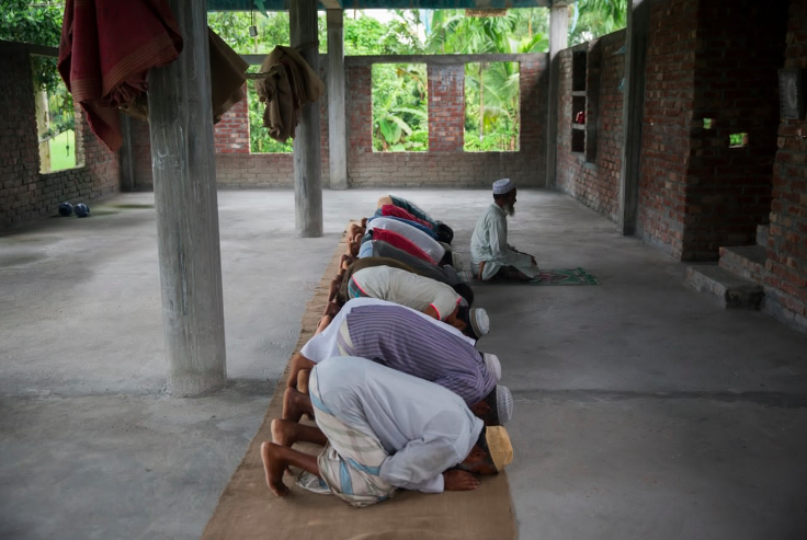 ABOVE: Muslim men from Dhoholakhagrabari enclave pray in their mosque. Mosques are usually the only solid structures that exist inside the enclaves.
