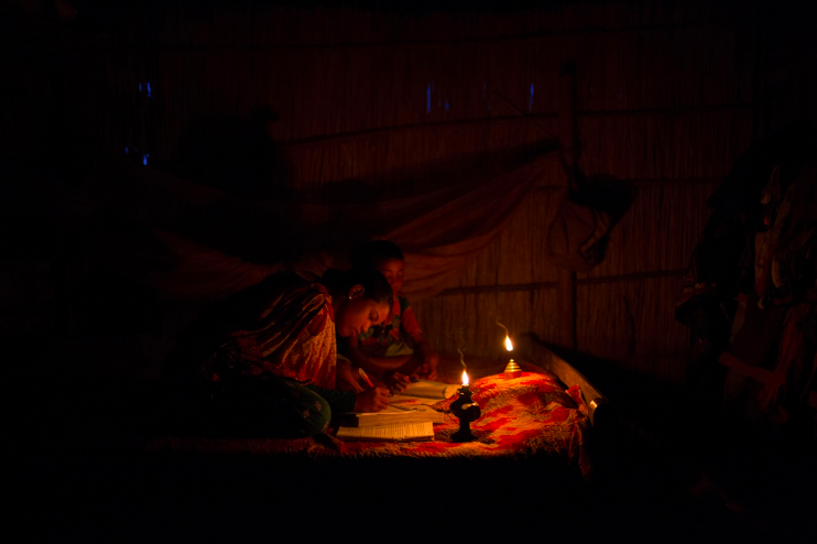 ABOVE: Sheltered within their small bamboo house, located inside the enclave of Dhoholakhagrabari, Eity Rani, 14, and Shobo Rai, 8, carefully do their homework by the light of an oil lamp. Life is much harder for children who are born in enclaves.