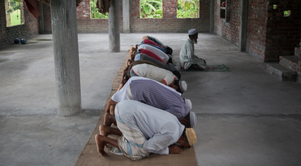 Muslim men from Dhoholakhagrabari enclave pray in their mosque. Mosques are usually the only solid structures that exist inside the enclaves.