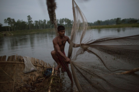 A man fishes at dusk using his large bamboo fish trap. This river exists just outside the enclave but as it's in Bangladesh territory, enclave dwellers are forbidden to fish here otherwise angering the local fishermen.