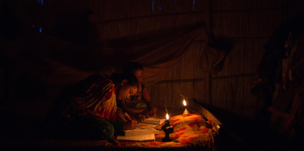 Sheltered within their small bamboo house, located inside the enclave of Dhoholakhagrabari, Eity Rani, 14, and Shobo Rai, 8, carefully do their homework by the light of an oil lamp. Life is much harder for children who are born in enclaves.