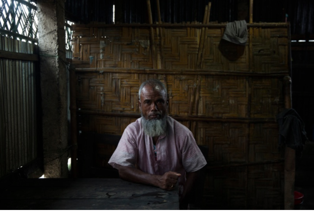 A Bangladeshi man sits in a shop in the market of a small town that sits between enclaves.