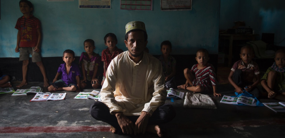 In Dhoholakhagrabari enclave students and their teacher sit in a madrassa class. Because enclave children have a difficult time accessing the education system in Bangladesh the locals of this enclave formed an Islamic Foundation funded on donations.