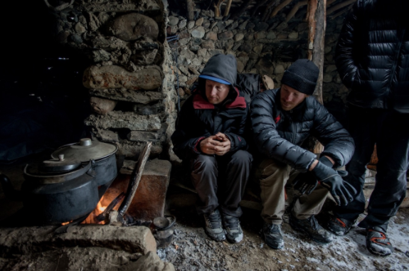 Pro rider Matt Hunter and cameraman Colin Jones huddle near the fire, inside a draughty shepherd's hut during a day of blizzards at Karabel camp, 4,300 metres.