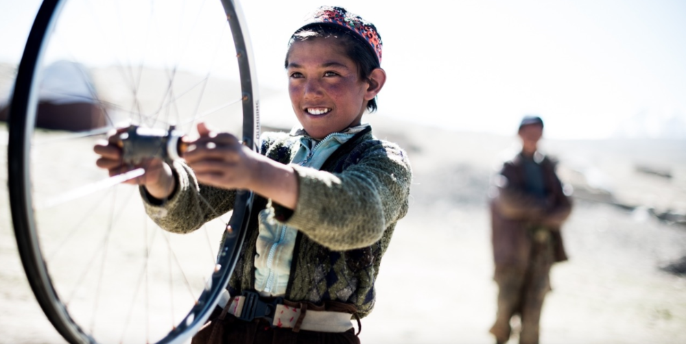 Fascinated, a young boy from the small village of Rabot in the Kyrgyz-populated Great Pamir, spins the wheel from one of our bikes.