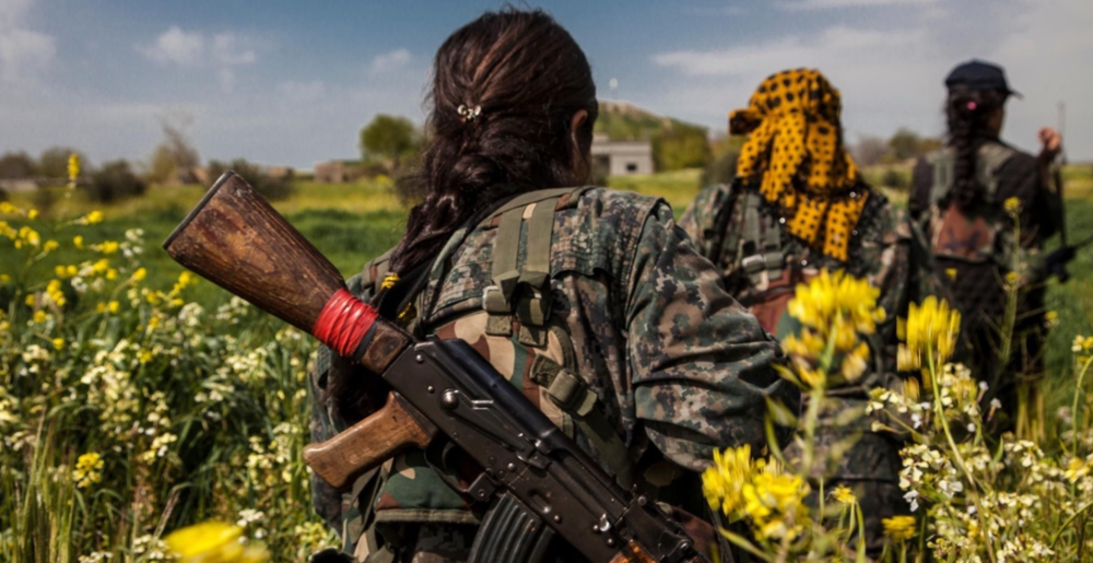 Three fighters from the YPJ walk through fields on the western front-line near the city of Kobanî on April 7, 2015.