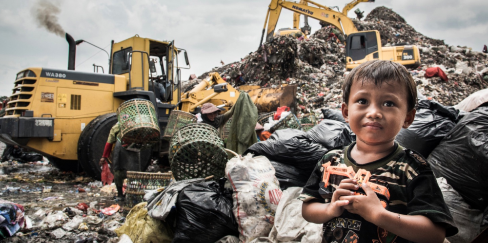 Amir, whose home is amongst these mounds of rubbish, waits for his mum who is working behind him. His favourite toy? A digger.