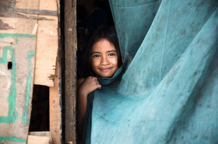 Nila, who lives with her family in a homemade shelter at the Bantar Gebang landfill, peeps out from behind a makeshift curtain.