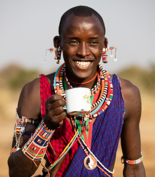 Lion Guardian Kikanai Ole Masarie celebrates the sighting of lioness Nenki's cubs with a fresh cup of tea. Note the Lion Guardians symbol hung around his neck, alongside his traditional handmade Maasai beads.