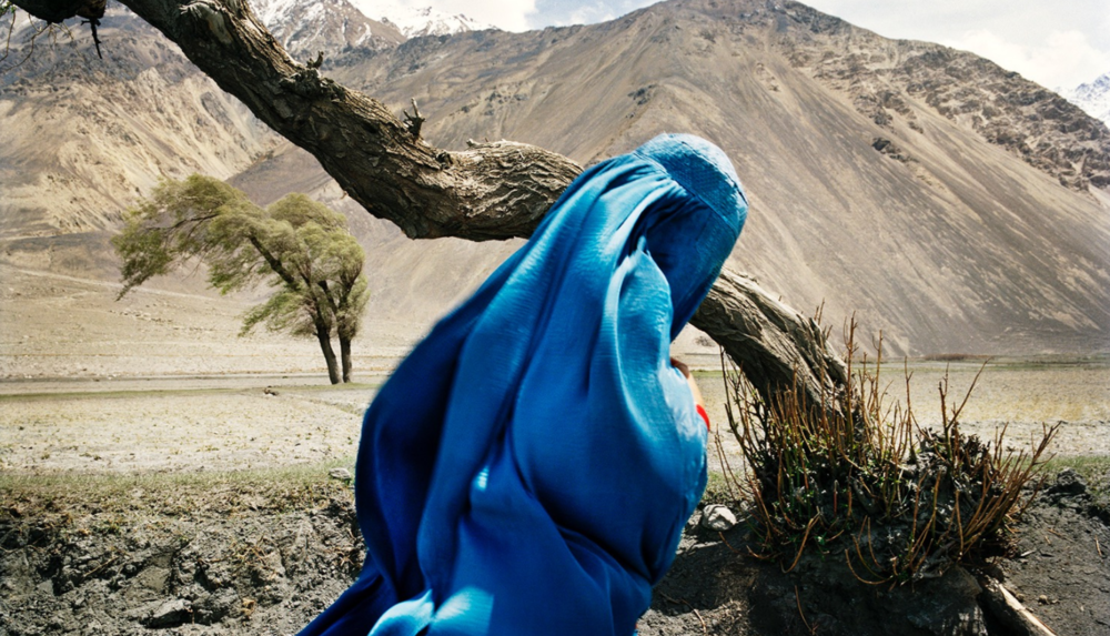 A veiled Sunni women makes her way back towards mainland Afghanistan from the Wakhan Corridor.