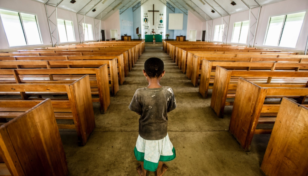 A young girl pauses to say a prayer as she enters a Christian church built by missionaries in the mountainous highlands of Papua New Guinea.