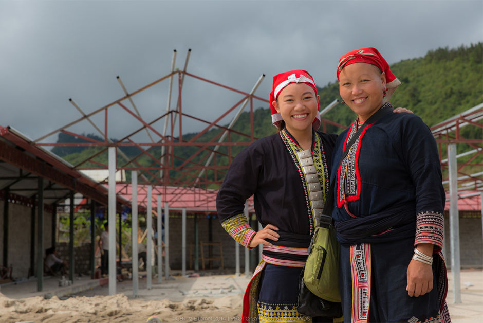 In Ta Phin village, sisters Ly Lo May and Ly Ta May stand in front of a new market under construction. Lo May helped raise over $12,000 to make this dream a reality for her community.