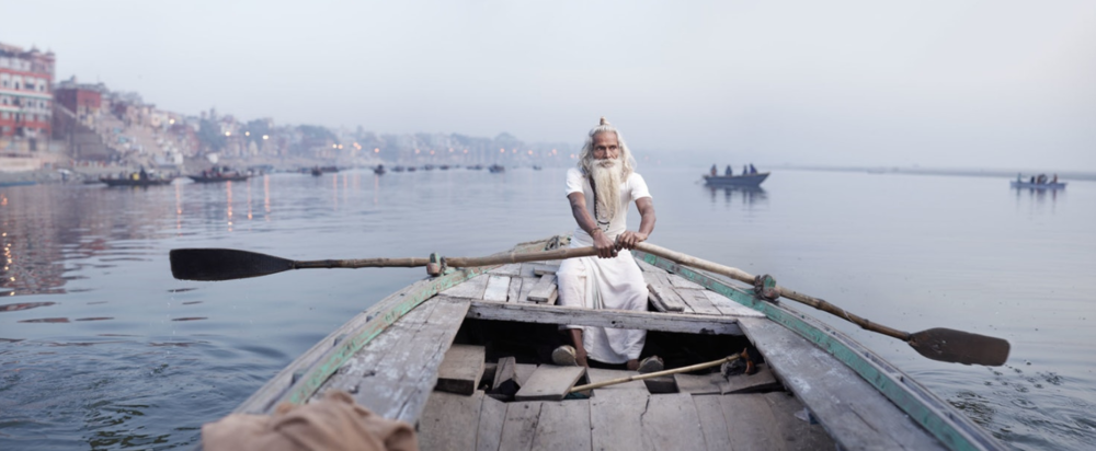 Ascetic priest Baba Vijay Nund rows a boat along the Ganges River.