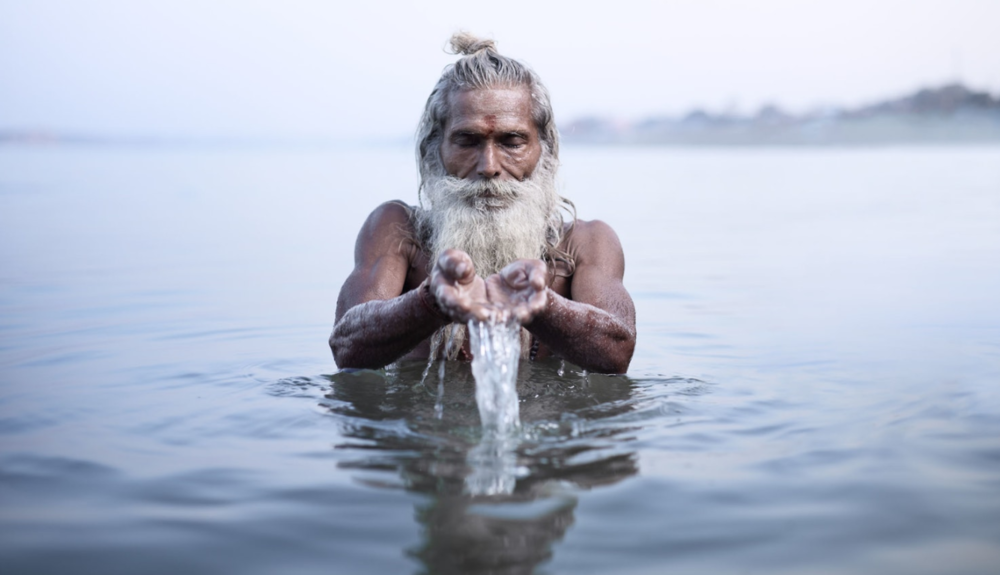 Vijay Nund performing morning rituals in the Ganges River, the most sacred river in Hinduism.