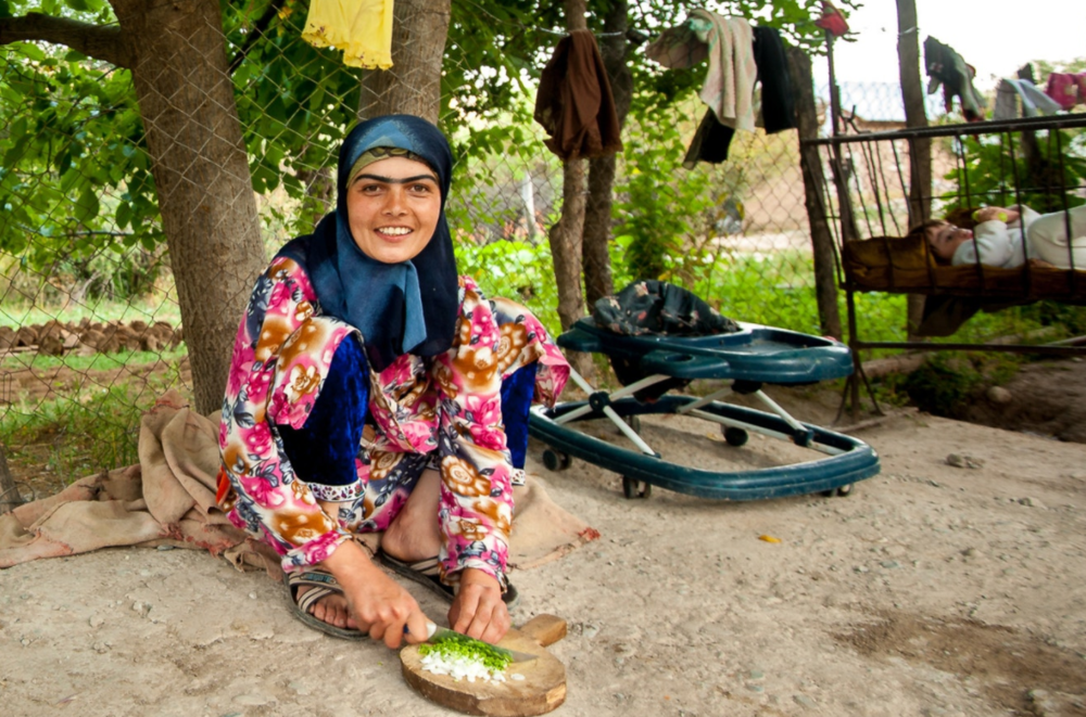 A young Tajik woman chops the fresh vegetables in preparation for the Ramadan feast after nightfall.