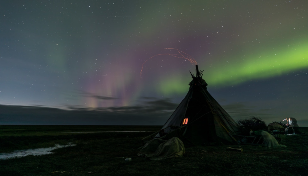 The Northern Lights arch high above the chum of the Khudi family, while sparks fly from the stove inside. Each year, the family must migrate to winter grazing lands with their reindeer, but without snow passage across the tundra is difficult to impossible.