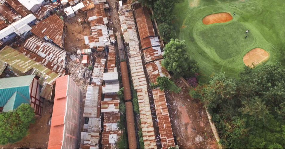 The Royal Nairobi Golf Club sits directly adjacent to Kibera slum. Twice a day, a passenger train barrels through the slum, less than a meter away from people's homes and businesses. Next door, people play the game surrounded by greenery.