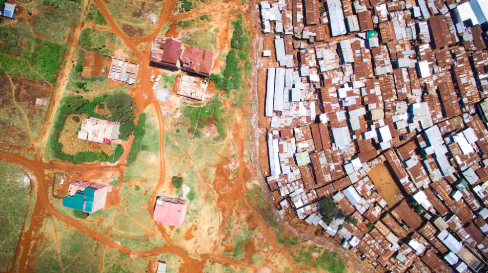 """Kibera is constrained not only by infrastructure but also the natural environment. The """"river"""" at the bottom of the slum drains thousands of tons of rubbish into the Nairobi Dam every year."""