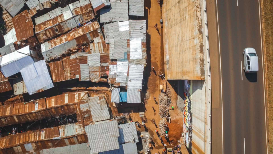 Cars glide over the brand new road, above the slum below.
