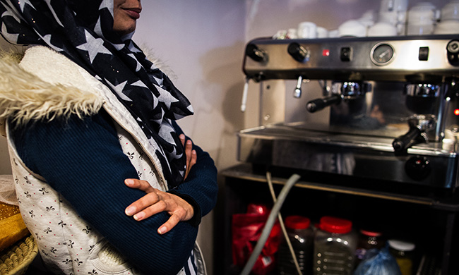 Inside Haidary's cafe, a female barista poses next to the coffee maker on March 19, 2017.Photos by Ivan Flores