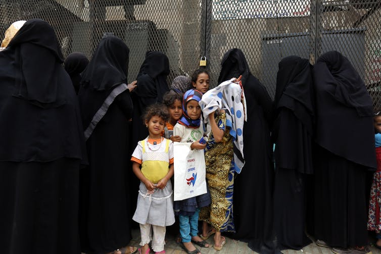 Yemeni women and girls wait to receive free bread provided by a charity bakery during a severe shortage of food in Sana'a, Yemen, 15 August 2017. EPA/YAHYA ARHAB