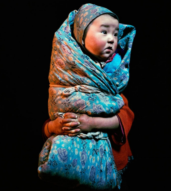 Wrapped baby, held by his sister, at Üüreg Lake in western Mongolia.