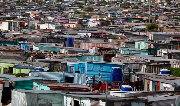 Residents walk through shacks in Cape Town's Khayelitsha township in this picture taken July 9, 2012.