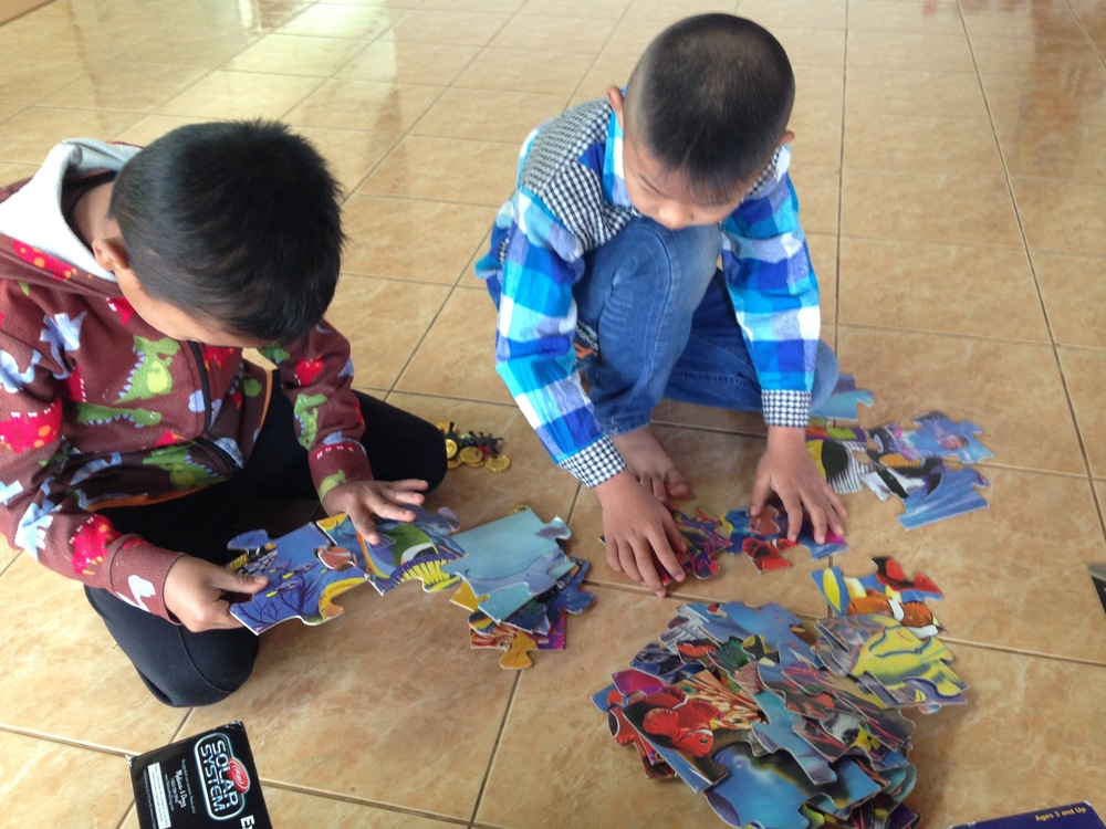Young boys working hard on a puzzle at an event we helped with last Saturday