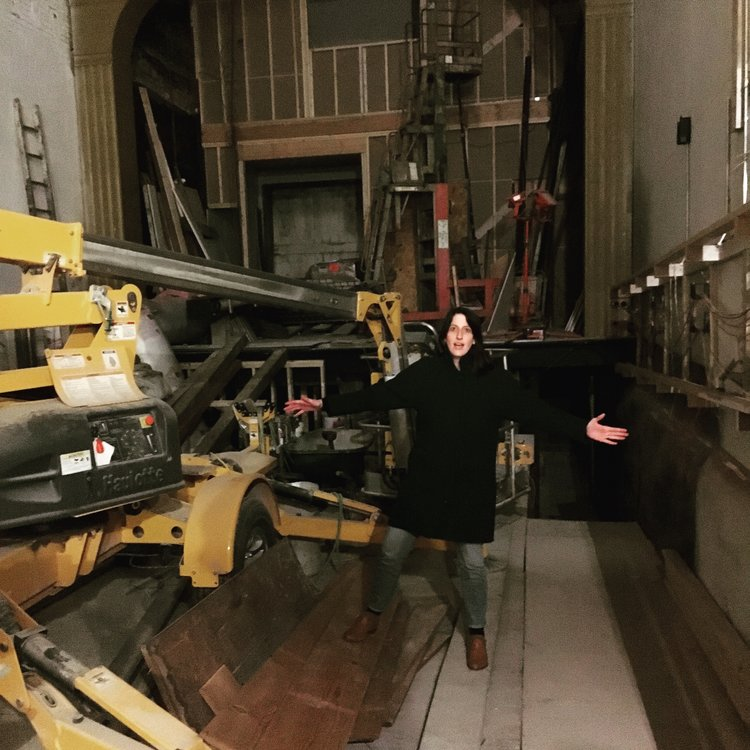 Rebecca Fons stands amongst the progress (note the huge man-lift in the middle of the theater floor). Bless this mess! March, 2017.