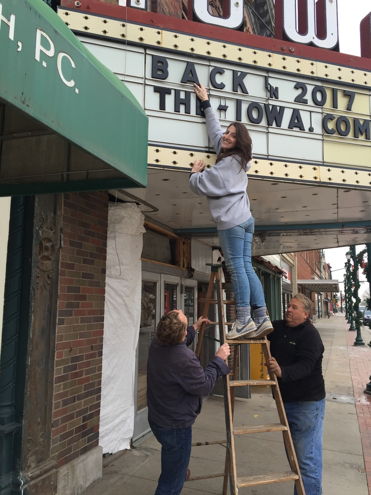 Rebecca Fons (with the support from Jack C. Newell and Steve Reed), tweaks the marquee letters announcing The Iowa's return, 2015.