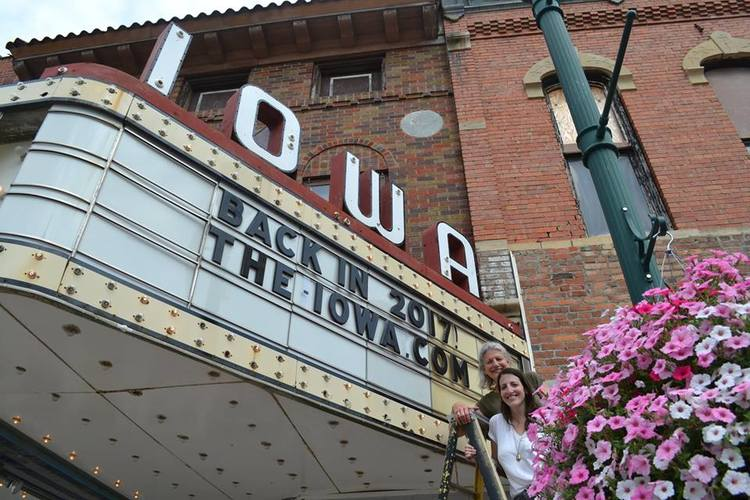 Marianne and Rebecca Fons stand in front of the marquee of The Iowa Theater after changing the marquee letters to announce the reopen. Photo courtesy of Wayne Davis.