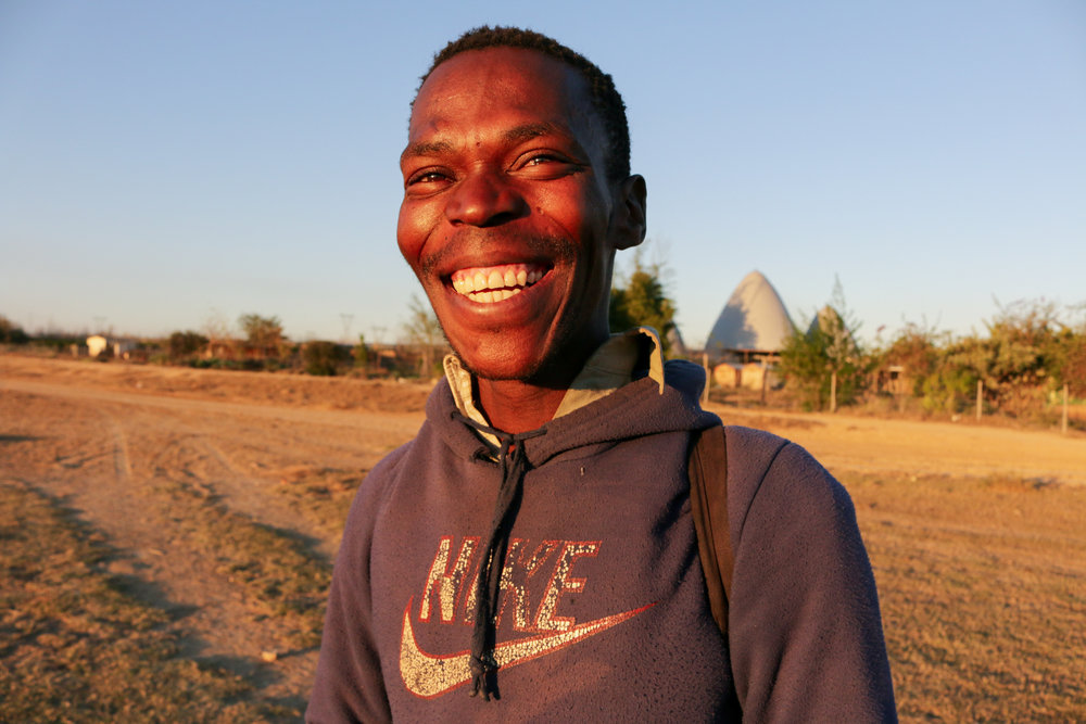 Luyanda, a member of the Langbos building team, standing proudly in front of the completed Langbos Children's Shelter, 2018.