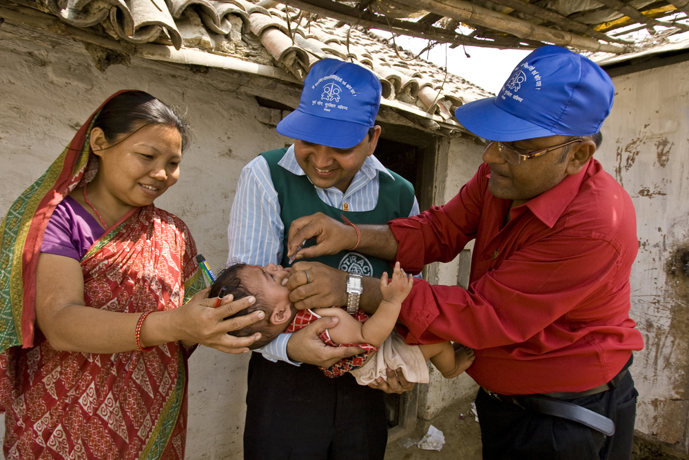 Rotaractor Abhishek Choudhary (center), holds a baby while Rotarian Om Prakash Sikaria administers the polio vaccine during polio immunization activities in Birgunj, Nepal.