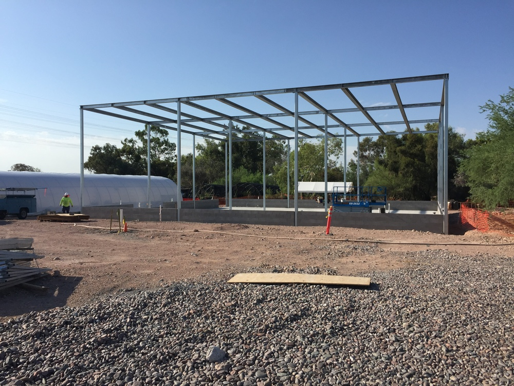 The structural framework for the greenhouse and external louver system is in place. One of the old Quonset Hut style greenhouses is visible on the left. This is a big upgrade.
