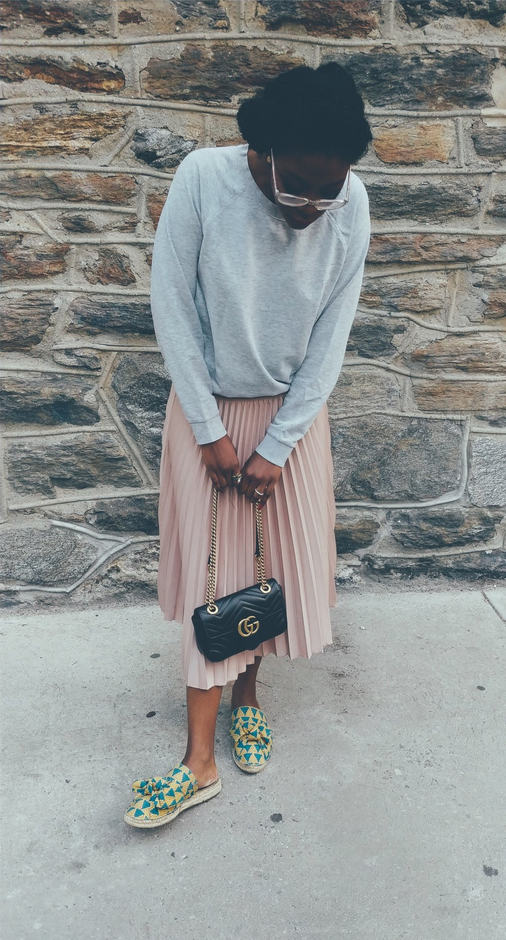 The casual sweatshirt makes the skirt less formal.