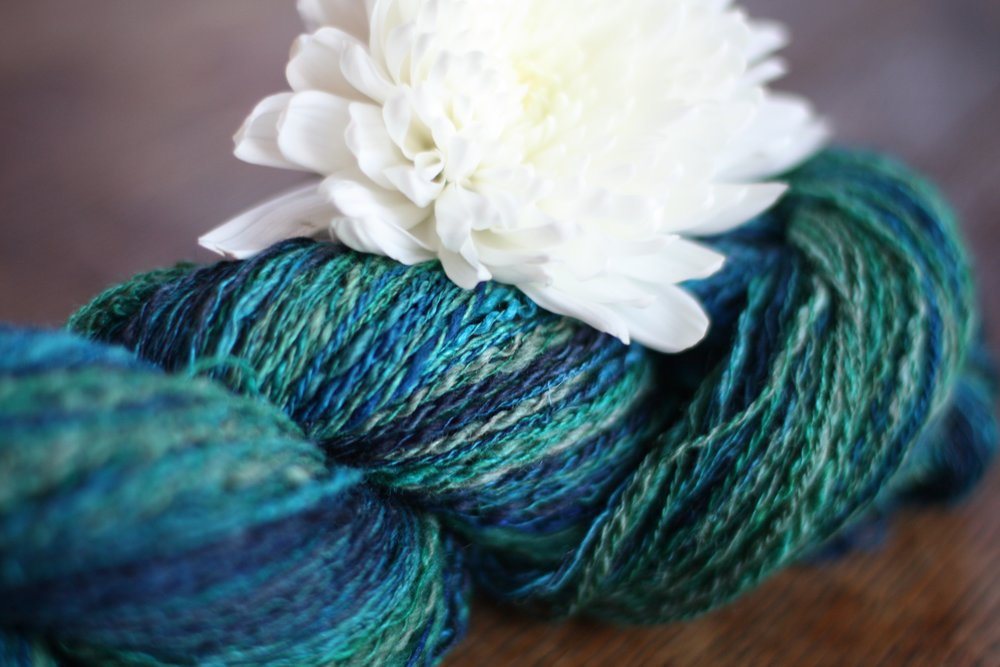 A skein of handspun wool/silk yarn in shades of blue and green rests on a weathered wooden table with a white flower | 14 Mile Farm Handweaving and Homesteading in Alaska
