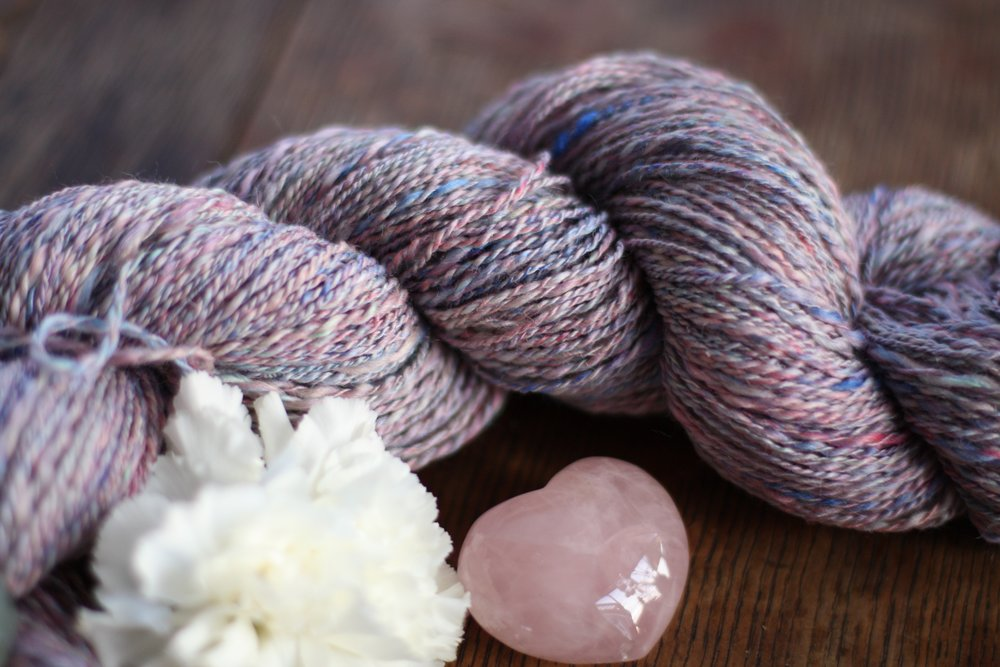 Rose quartz heart rests next to a handspun skein in ethereal tones of pinks and blues | 14 Mile Farm Handweaving and Homesteading