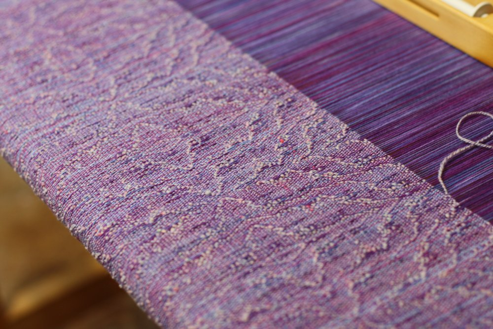 Cloth on the loom, handspun weft adds so much visual to texture to this piece of Sugar Plum Fairy | 14 Mile Farm Handweaving and Homesteading