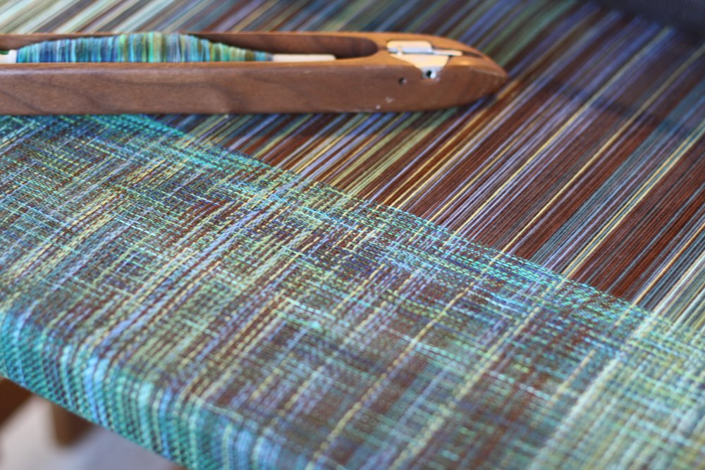 The play of hand dyed weft against pinstriped warp gives the appearance of sunlight on the changing surface of the ocean | 14 Mile Farm Handweaving and Homesteading