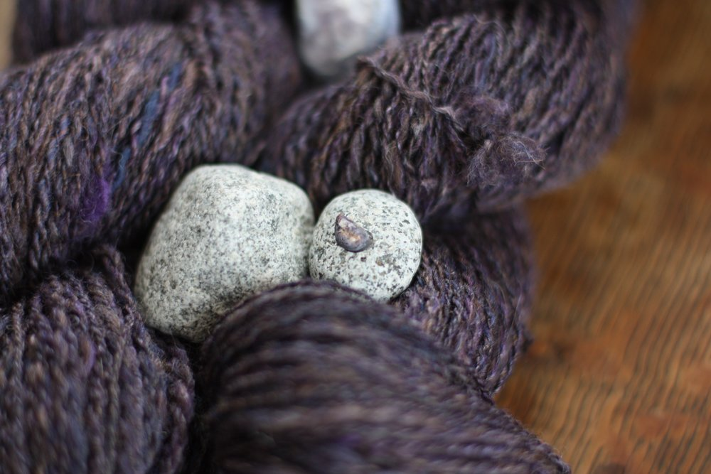 A teeny tiny miniscule mussel shell rests on a granite stone which rests on two skeins of handspun yarn.  The colors of the shell and the colors of the yarn match perfectly | 14 Mile Farm Handweaving and Homesteading in Alaska